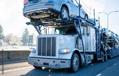 Big rig car hauler semi truck transporting cars on two levels semi trailer drivi Wallpaper Mural