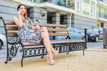 Girl In A Sundress Sits On A Bench