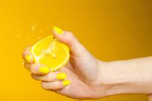 Hand With Yellow Fingernails Crushing A Fresh, Juicy Lemon
