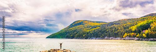 Naklejka premium Jesień spadku natury krajobrazu gór sztandaru tło w Quebec, Kanada. Rzeka Świętego Wawrzyńca w regionie Charlevoix, Ameryka Północna. Osoba turystyczna z bronią do góry w wolności szczęśliwy z wakacji podróży.