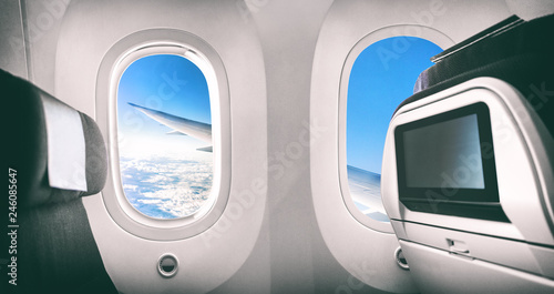 Airplane passenger seat plane interior with window view of flying aircraft wing and movie screen.