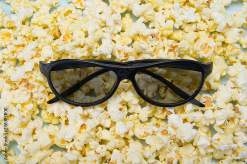 against the background of scattered popcorn are 3 d glasses, close-up