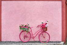 Bright Pink Bike With Flowers In Its Baskets Outdoors