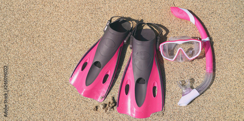 Snorkel equipment lying on beach sand background - pink scuba diving mask and fins icon for travel vacation concept.