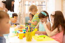 Group Of Kindergarten Children Play With Plasticine Or Dough. Little Kids Have A Fun Together With Colorful Modeling Clay At Daycare.