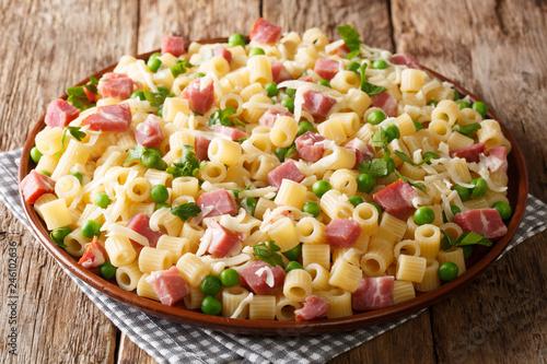 Homemade salad Ditalini pasta with green peas, ham and cheese closeup on a plate. horizontal