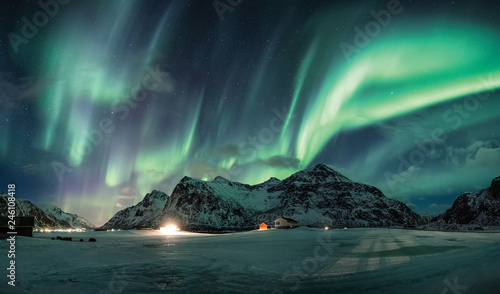 Wall Murals Northern lights Aurora borealis or Northern lights over snow mountain on coastline