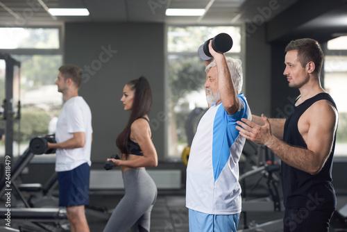 Fototapeta Elderler serious man training in crowded gym. obraz na płótnie
