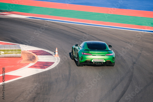 Beautiful green race car rides along race track