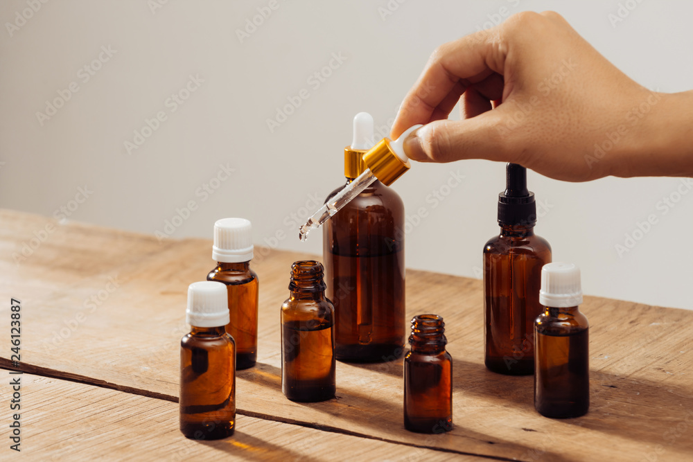 Fototapety, obrazy: Essential oils bottles on wooden desk with candlelight beside. Spa wellness set.