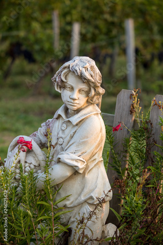 Poster Historisch mon. Statue of a boy holding a basket with grapes on the background of vineyards in the Saint Emilion region. France