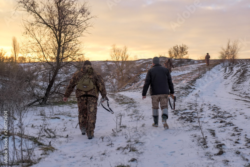Winter hunting for hares. People with Shotguns looking for pray.