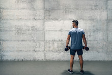 Man Holding Dumbbells While Standing With Backs Turned. If It Was Easy, Everyone Would Do It.