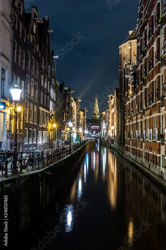 Photo  view of a water canal in Amsterdam during the night with a lot of bikes parked
