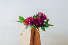Pink Peonies In A Paper Bag On A White Table