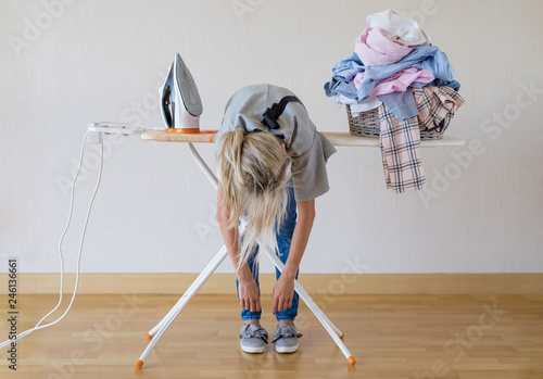 Fotografiet Exhausted woman lying on ironing desk