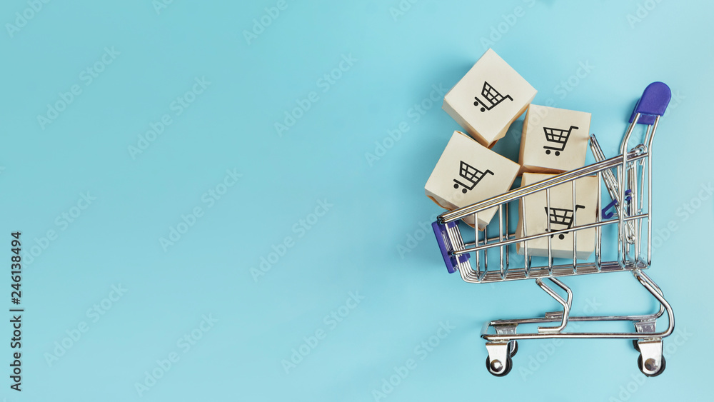 Fototapeta Boxes in a shopping cart on blue background. Concept: online shopping, e commerce and delivery of goods. Copy space.