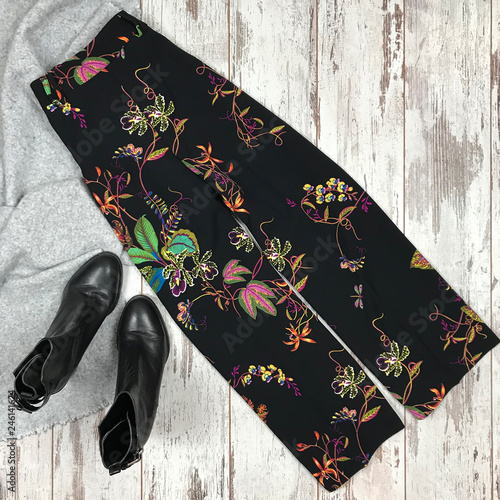 Fotografie, Obraz  Female black trousers in a print of flowers on a wooden background