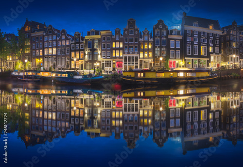 Fotografiet Cityscape of Amsterdam at night with reflection of buildings on water