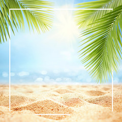 Summer background with frame, nature of tropical golden beach with rays of sun light and leaf palm. Golden sand beach close-up, sea water,  blue sky, white clouds. Copy space, summer vacation concept.