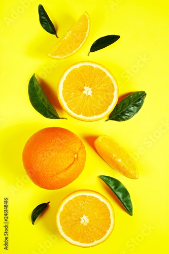 Close up image of juicy organic whole and halved oranges with green leaves & visible core texture, isolated yellow background, copy space. Macro shot of bright citrus fruit slices. Top view, flat lay.