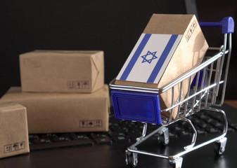 Paper box with a flag of Israel in a shopping cart on a laptop keyboard. International E-commerce