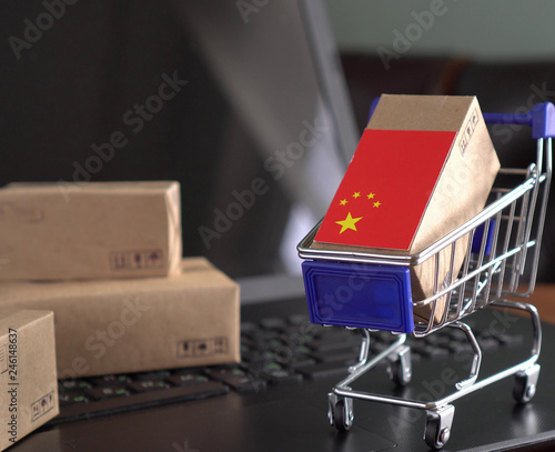 Photo  Paper box with a flag of China in a shopping cart on a laptop keyboard