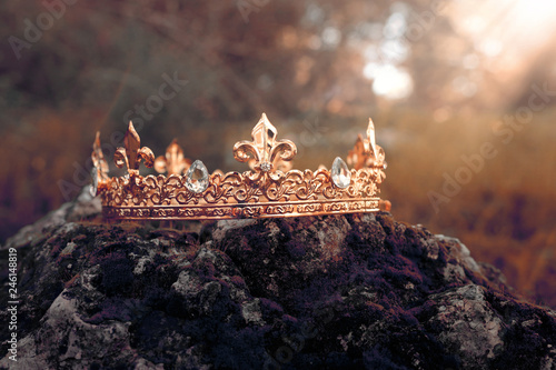 Foto  mysterious and magical photo of gold king crown over the stone covered with moss in the England woods or field landscape with light flare