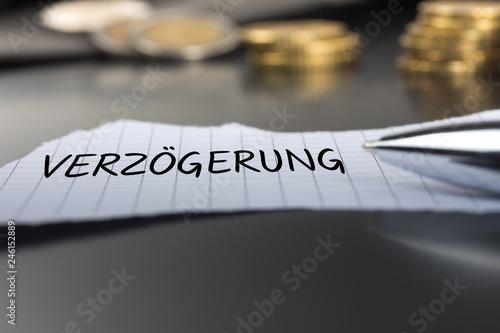 Fotografie, Obraz  Verzögerung auf einem Zettel mit Stift vor Geldmünzen