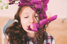 Dreamy Smiling Kid Girl Smells Orchid Flower At Home
