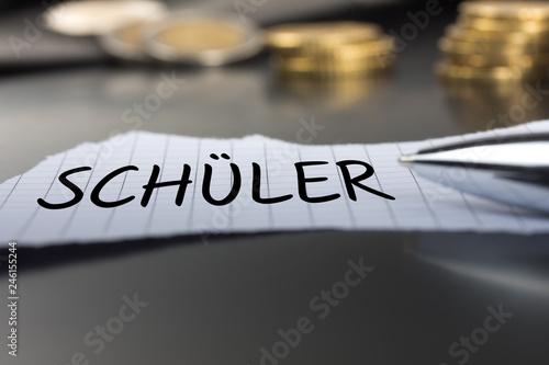 Fotografía  Schüler auf einem Zettel mit Stift vor Geldmünzen