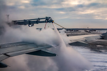 A Process Of Spraying Anti-icing White Fluid The Rear Part Of The Wing Of A Plane At The Airport At Sunrise In Winter On The Blue Sky With Pink Clouds Background