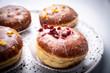 Cukiernia, tradycyjne pączki z lukrem. Apetyczne słodkie ciastka na kuchennym stole.