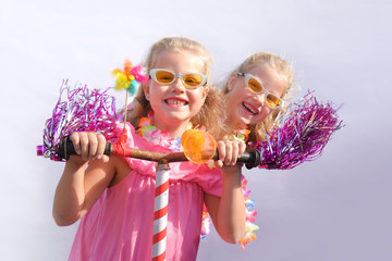 Twin sisters play together riding an imaginative bicycle. They use a rusty handlebar they found in the garage. They fit it with fringes, a windmill and an orange plastic horn.