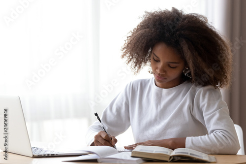 Fotografia Focused African American teenage girl sit at table with laptop studying with han