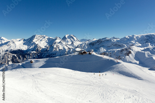 Slope on the skiing resort in Alps, France. Sunny winter day. Winter vacation