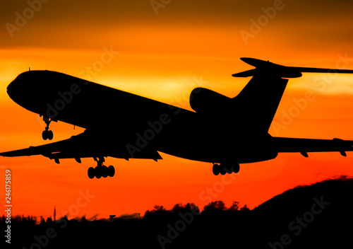 Fotografia  Takeoff of a passenger plane on the background of a sunset.