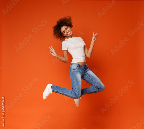 Foto  African-american joyful lady jumping and gesturing peace