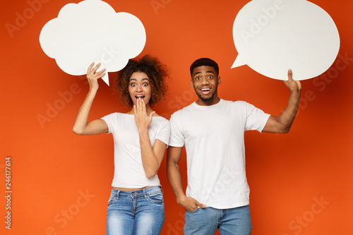 Young black couple holding communication bubbles at studio