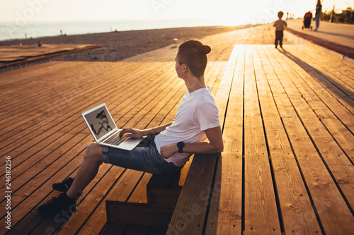 Valokuva  Side view - a slim young student boy sits near the beach on wooden benches and admires the view while studying with a laptop on a sunny summer day