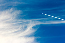 Blue Sky Background With Contrails And Clouds