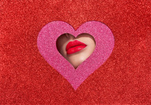 Beautiful Plump Bright Lips Of A Young Beautiful Woman With Red Lipstick Look Into The Pattern Of Heart Shaped Made Of Colored Paper. Holiday Patterns. Valentine's Day. Beautiful Love Make-up