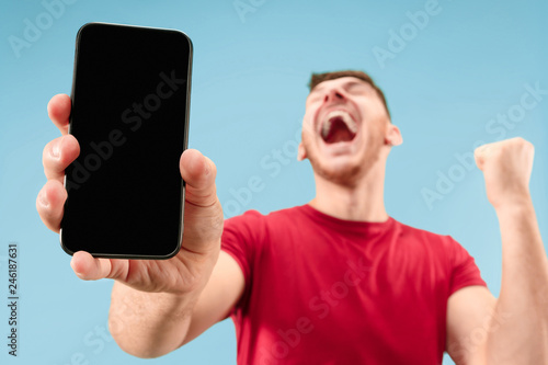 Obraz Young handsome man showing smartphone screen over blue background with a surprise face. Human emotions, facial expression concept. Trendy colors - fototapety do salonu