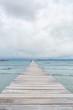 Ein heller Steg erstreckt sich übers Meer bis zum Horizont, der Himmel bewölkt, hochkant