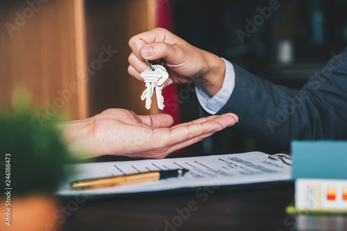 Fotografía  estate agent giving house keys to woman and sign agreement in office