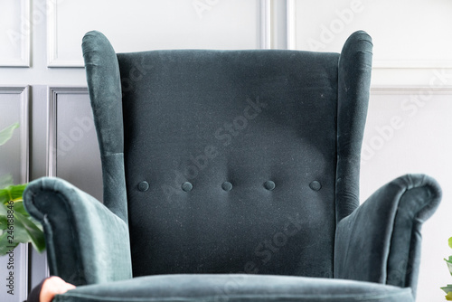 Fototapeta Close up high back green velvet armchair with gray painted wall in the backgroun