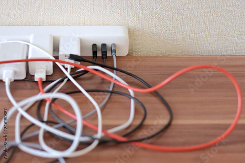 Fotografie, Obraz Blurred tangled colorful electricity, usb cables on wooden table