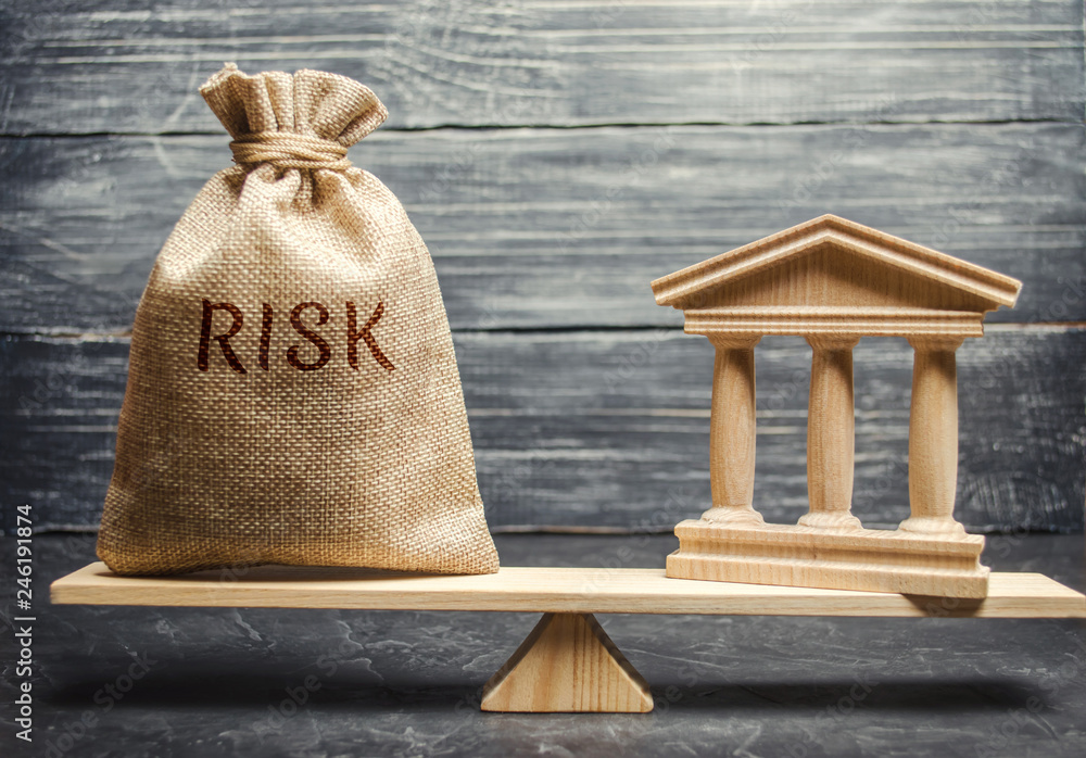 Fototapeta A money bag with the word Risk and a bank building on the scales. The concept of financial and economic risk. Unreliable investment. Unpaid loan. Financial risk management. Commercial loan