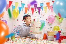 Boy Blowing Candles From A Bir...