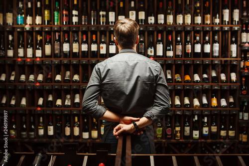 Bartender at wine cellar full of bottles with exquisite drinks Canvas Print